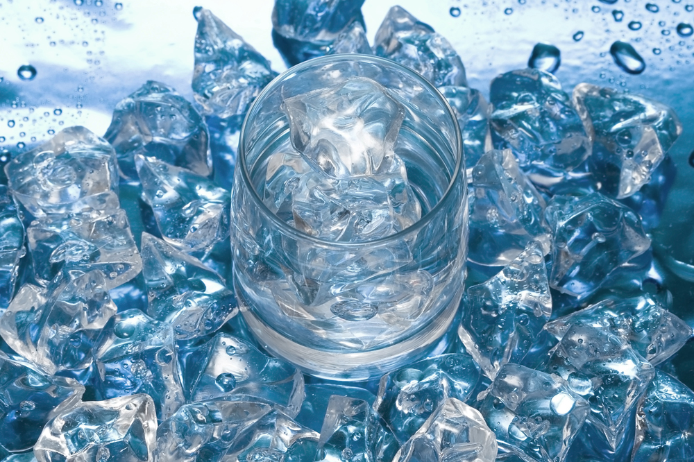 Glass with water and ice over blue